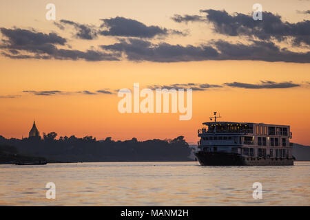 Silhouette of a touristic boat at sunset with the Shwezigon pagoda in background. Nyaung U, Bahgan, Myanmar (Burma). - Stock Photo