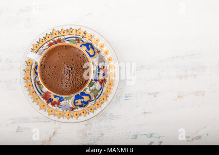 Vintage cup of Turkish coffee on a saucer over wooden surface background, viewed overhead with copy space to the side - Stock Photo