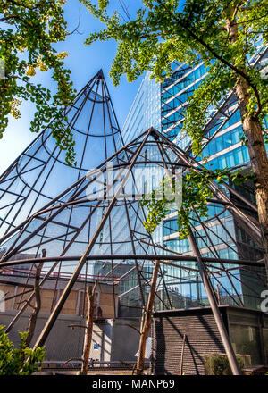 Berlin Charlottenburg, Neue Kranzler Eck complex.Urban abstract of modern glass & steel buildings and triangular-prism bird cage - Stock Photo