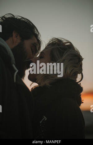 Young happy couple close up portrait while they get closer to each other and kiss. - Stock Photo