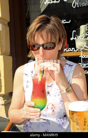 Woman / lady sitting outside in the sunshine at a cafe bar enjoying drinking  a colourful cocktail through a straw in the  city of Budapest Hungary - Stock Photo