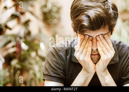 Young man sitting covering his eyes with his hands, sad and depressed concept. - Stock Photo