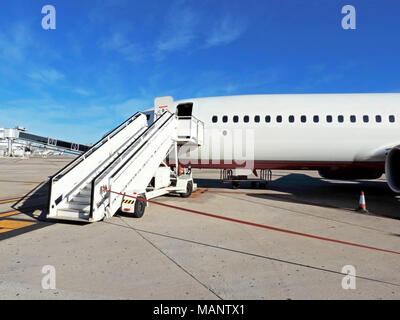 Airplane entrance with stairway and boundary. Landed plane, parking position on the airfield. - Stock Photo