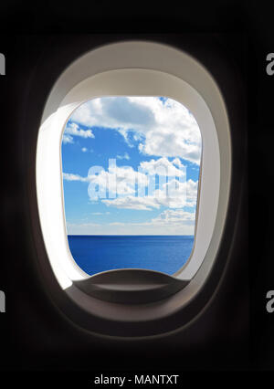 Airplane porthole, view outside an airplane window to blue sky and clouds. - Stock Photo