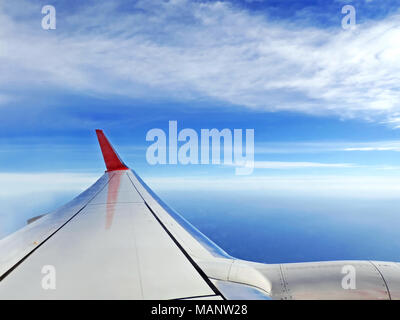 Airplane view, traveling by plane. View outside an airplane window to the airplane wing and blue sky and sea. - Stock Photo