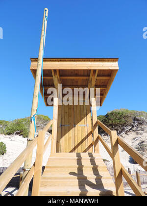 Rescue tower or wooden watchtower on the beach. Lifeguard tower in the sound with blue sky and beach dunes. - Stock Photo