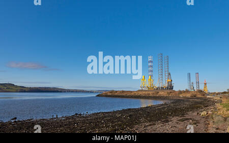 Looking across the Tay Estuary towards Fife, with the Tay Bridges and Dundee Port with Rigs and Cranes in the background. - Stock Photo