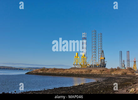 The southern end of Dundee Port from the Grassy Beach along the Green Circular Walking and Cycling Route, showing the Jack Up Rigs and Sheerleg Crane  - Stock Photo