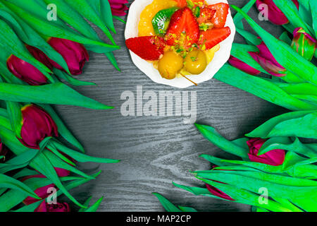 beautiful fresh spring tulip and fruit cake on dark background. Flower gift with sweet delicious - Stock Photo