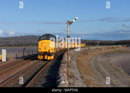 Colas Railfreight class 37 locomotives  passing a mechanical semaphore signal at Arnside with a Network rail infrastructure monitoring train - Stock Photo