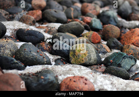 Colorful rocks laying on a ground. In between the stones there is some snow and ice. Photo is taken in Finland during spring season. - Stock Photo