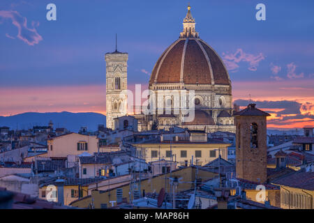 Cupola and bell tower of cathedral Santa Maria del Fiore in Florence, Itlay. Church iluminated by lights in the dusk. Beautiful pink and blue sky. - Stock Photo