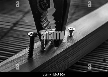Monochrome scattered screws screwed into the wooden plank and pliers. - Stock Photo