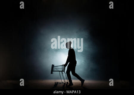 young male in casual clothers drawing an empty cart on the street - Stock Photo