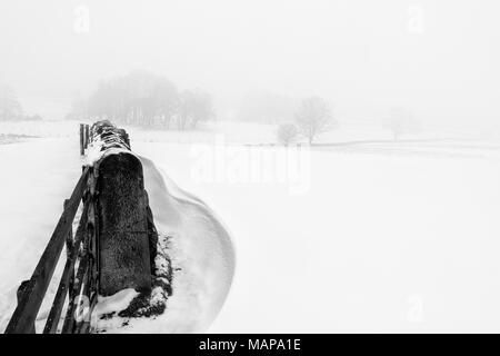 Simple monochrome image of a snowy scene of fields in the countryside with snowdrifts and a stone wall - Stock Photo