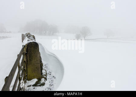 Simple image of a snowy scene of fields in the countryside with snowdrifts and a stone wall - Stock Photo