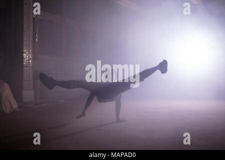 b-boy standing on arm and swinging the legs around on the street - Stock Photo
