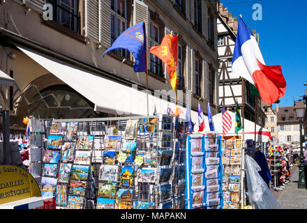 Postcards for sale on display stands, flying French flag, place de la Cathédrale, cathedral square, Strasbourg, Alsace, France, Europe, - Stock Photo