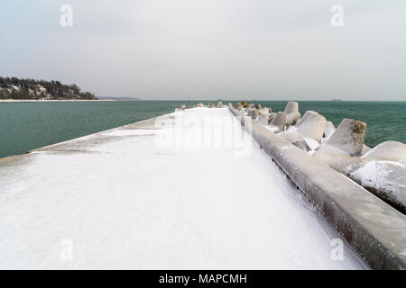 Concrete pier with ice and snim in Varna, Bulgaria - Stock Photo