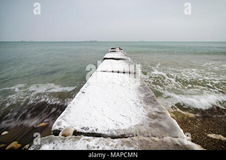 Concrete pier with ice and snow in Varna, Bulgaria - Stock Photo