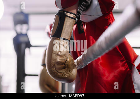 beaten boxer in yellow boxing gloves leaning on ropes - Stock Photo