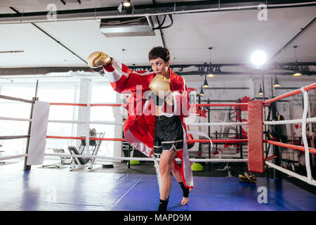beautiful model fighting with opponent in yellow boxing gloves in sparring ring - Stock Photo
