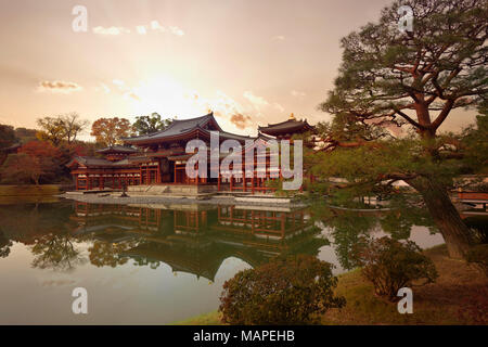 Beautiful dramatic sunset autumn scenery of the Amida hall of Byodo-in temple on the pond of Jodo-shiki Pure Land garden. Uji, Kyoto Prefecture, Japan - Stock Photo