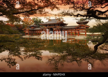 Colorful red sunset scenery of the Phoenix Hall, Amida hall or Hoo-do of Byodoin Buddhist temple amidst Jodoshiki teien, Pure Land garden pond visible - Stock Photo