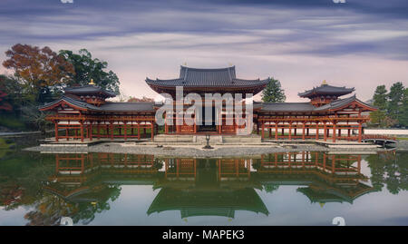 Beautiful Amida Hall of Byodoin Japanese Buddhist temple reflecting in the water of Jodoshiki Pure Land garden pond in a peaceful autumn morning scene - Stock Photo