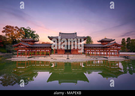 Beautiful tranquil sunset scenery of the Phoenix or Amida Hall of Byodoin, Byodo-in Japanese Buddhist temple reflecting in the clear calm water of Jod - Stock Photo