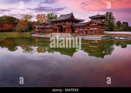 Peaceful autumn scenery of the Phoenix Hall, Amida hall of Byodoin temple on Kojima island of Jodoshiki teien, Pure Land garden pond. Uji, Kyoto Prefe - Stock Photo