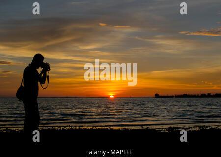 silhouette man photographing sea against sunset - Bintan island, Indonesia - Stock Photo