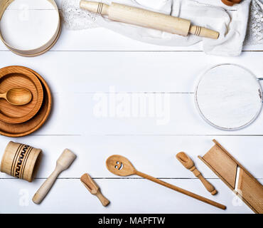 wooden round plates, sieve and rolling pin, round cutting board and other kitchen items on a white table, top view, empty space in the middle - Stock Photo