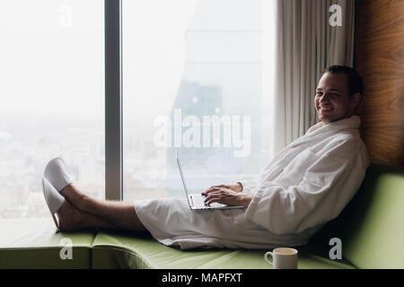Young smiling businessman working on laptop computer wearing white bath robe sitting near window with cup of coffee looking at sunrise city view. Motivation concept - Stock Photo