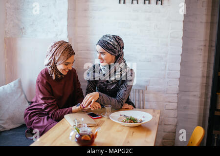 Two Muslim women in cafe, friends meeting - Stock Photo