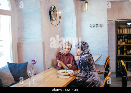 two business partner using tablet in front of their coffee shop - Stock Photo