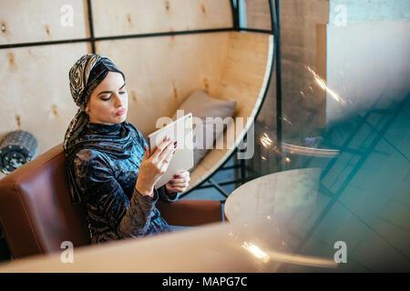 beautiful Arabic Muslim girl using tablet in cafe - Stock Photo