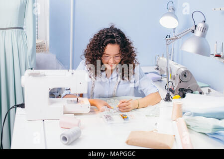 tailor embroidering at the table on workshop - Stock Photo
