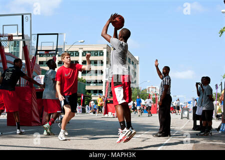 A young man shoots a jump shot in a 3-on-3 basketball tournament held on the streets of downtown Athens, on August 24, 2013 in Athens, GA. - Stock Photo