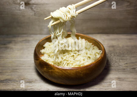 Instant noodles in wooden plate on wooden background - Stock Photo