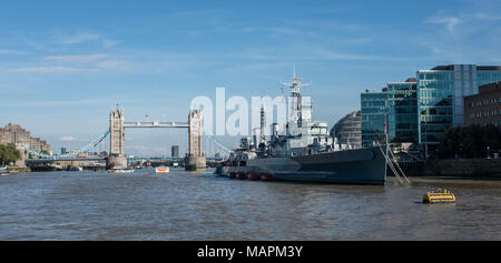 HMS Belfast moored on Southbank of Thames with Tower Bridge in background, London, England - Stock Photo