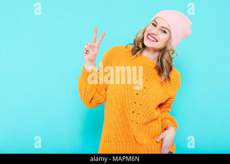 Crazy beautiful trendy girl in mustard coloured sweater and pink beanie hat making peace sign hand gesture. Attractive cool young smiling woman . - Stock Photo