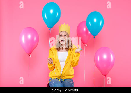 Funny girl in birthday hat, balloons and blowout horn on pastel pink background. Attractive trendy teenager celebrating birthday. - Stock Photo