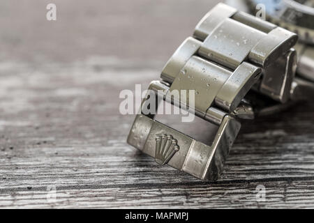 Close-up view of a well-known, Swiss manufactured men's mechanical divers watch showing detail of the adjustable bracket and steel clasp. - Stock Photo