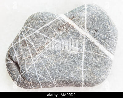 macro shooting of natural mineral rock specimen - Greywacke sandstone on white marble background - Stock Photo