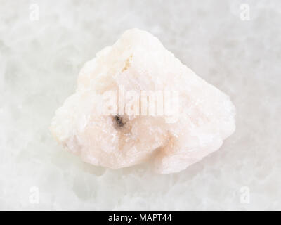 macro shooting of natural mineral rock specimen - rough Barite stone on white marble background - Stock Photo