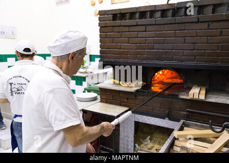 Man cooking traditional Italian pizza in a wood-fired oven at L'Antica Pizzeria Da Michele, Naples, Italy - Stock Photo
