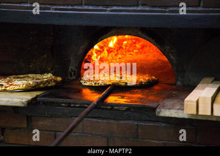 Pizza coming out of the wood-fired oven at the famous L'Antica Pizzeria Da Michele in Naples, Italy - Stock Photo
