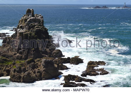 this is a photo of water crashing onto a big rock formation. - Stock Photo