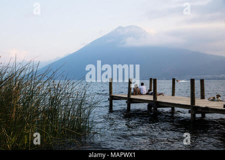 San Marcos, Lake Atitlan, Guatemala - March 30 2018: three tourists and a dog sitting on the pier for watching sunset with volcano San Pedro in the ba - Stock Photo